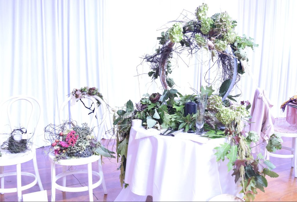 A wreath of greenery on a table